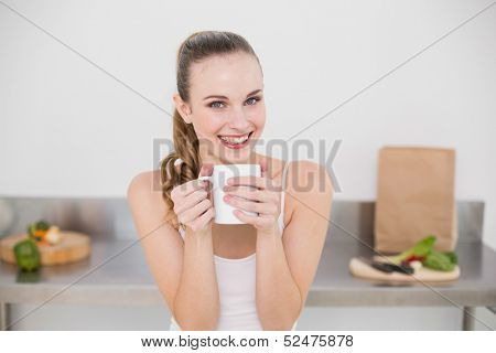 Smiling young woman holding mug in the kitchen at home