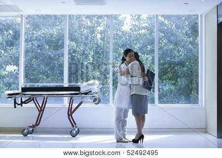 Doctor and patient hugging in a hospital next to a stretcher