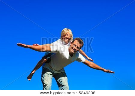 Young Boy On Father's Back Playing Airplane