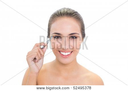 Smiling brunette woman plucking her eyebrows on white background