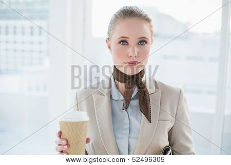Blonde content businesswoman holding disposable cup in bright office