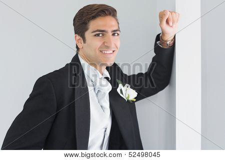 Handsome bridegroom leaning against a wall smiling at camera