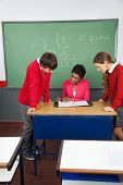 Young female teacher teaching teenage students at desk in classroom