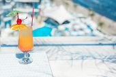 stock photo of infinity pool  - The orange cocktail near the swimming pool - JPG