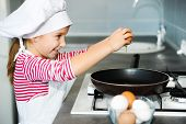 pic of ooze  - happy little girl cracking an egg over pan - JPG