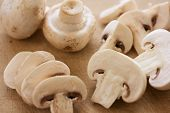 stock photo of edible mushroom  - Whole sliced and chopped white button mushrooms on a wooden chopping board - JPG