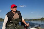 stock photo of outboard  - man steers the boat with outboard motor - JPG