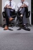 Two businessmen sitting down with legs crossed