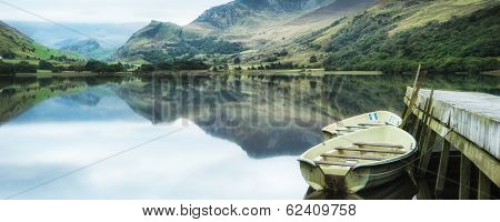Panorama Landscape Rowing Boats On Lake With Jetty Against Mountain Background
