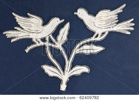 Antique birds embroidery on blue background