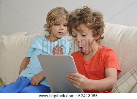 young boys playing games on a tablet