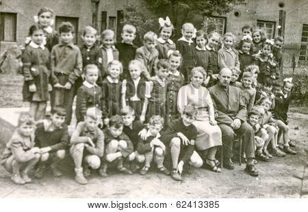 LODZ,POLAND, CIRCA 1950's: Vintage photo of group of  classmates and teachers posing together  in front of the school