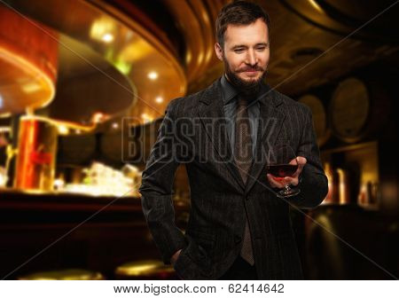 Handsome well-dressed man in jacket with glass of beverage in restaurant interior