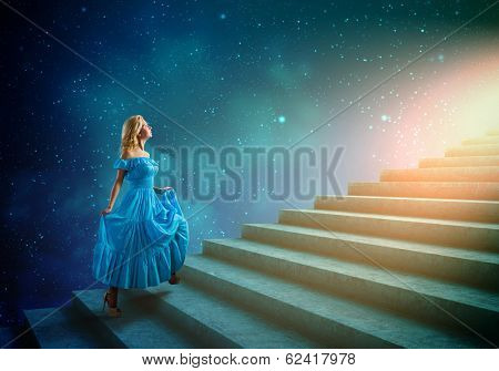 Young blond woman in blue dress walking up the stairs
