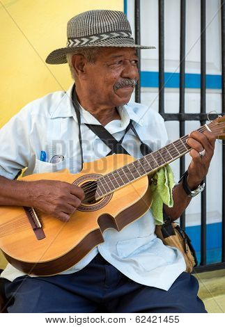 HAVANA, CUBA - FEBRUARY 25, 2014: Street musician playing traditional cuban music on an acoustic guitar for the entertainment of tourists in a typical colorful Old Havana street