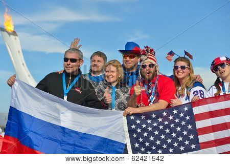 SOCHI, RUSSIA - FEBRUARY 12, 2014: Russian and American fans with flags in the Olympic Park during XXII Winter Olympics against Olympic flame. Russia hosts the second Olympic Games in history
