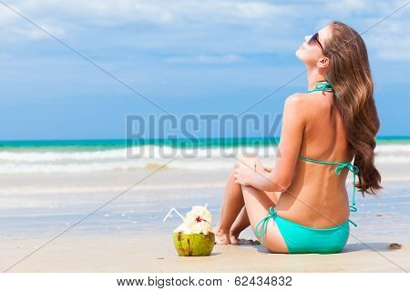 Happy young long haired woman in bikini and sunglasses with coconut on the beach