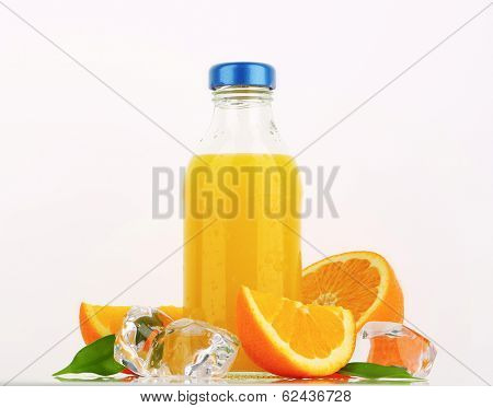 bottle of  orange juice with fresh oranges and frozen ice cubes