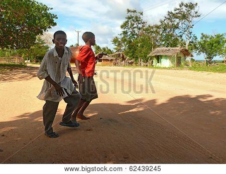 Lindi, Tanzania - Desember 2, 2008: Two Unfamiliar Boys Cross The Road.