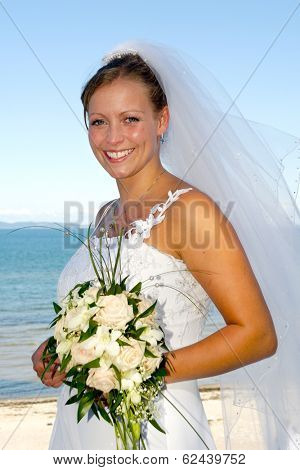 Happy wedding bride is holding a bouquet and is smiling.