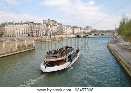 PARIS, FRANCE - MARCH 18, 2014: An excursion boat heads towards the Pont De La Tournelle on the River Seine. Numerous such boats ply the Seine each day, passing many famous Paris landmarks.