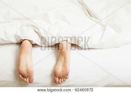 Woman's feet sticking out of blanket on bed at home
