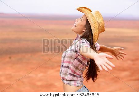 Cowgirl - woman happy and free on american prairie wearing cowboy hat with arms outstretched in freedom concept. Beautiful smiling multiracial Caucasian Asian young woman outdoors, Arizona Utah, USA.