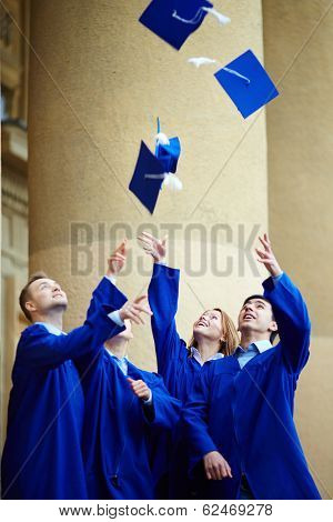 Group of smart students in graduation gowns throwing their hats