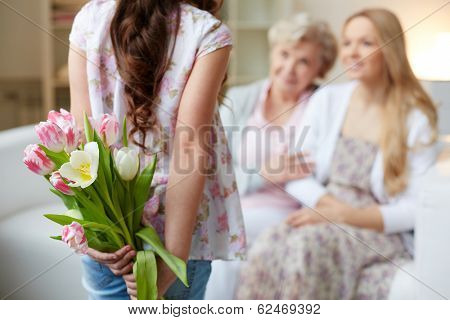Rear view of little girl holding bunch of flowers behind back with her mother and grandmother on background