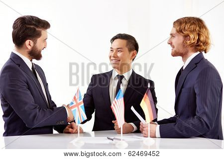 Image of three partners handshaking after negotiations with American, British and German flags and business documents on foreground