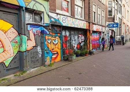 Amsterdam, Netherlands - March 19, 2014: Street With Colorful Graffiti On Building Facades