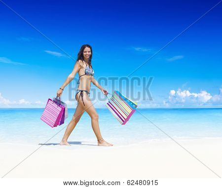 Woman with shopping bags on the beach.