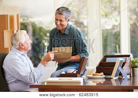 Senior Father Discussing Document With Adult Son