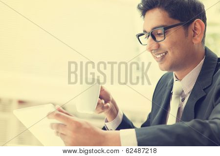 Young Asian Indian businessman using a tablet computer during office break at cafe, relaxing with a cup of coffee. India male business man,  in vintage retro style.