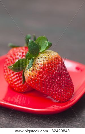 Red Juicy Strawberry In Red Plate On A Wooden Surface