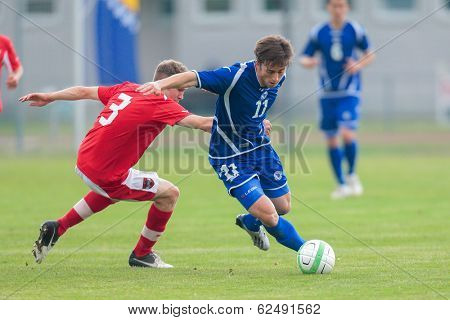 TRAISKIRCHEN, AUSTRIA - JUNE 5  Lukas Jaeger (#3 Austria) and Armin Cerimagic (#11 Bosnia and Herzegovina) fight for the ball during the U19 game on June 5, 2013 in Traiskirchen, Austria.