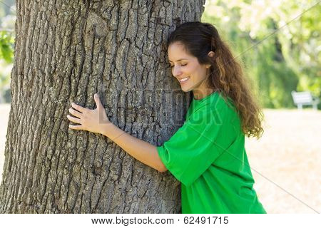 Beautiful young environmentalist embracing tree trunk in park