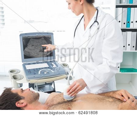 Female cardiologist using sonogram on male patient in examination room