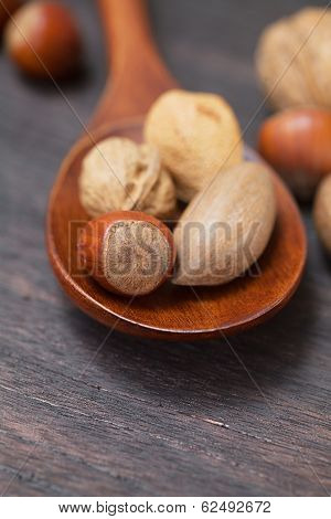 Wooden Spoon With Nuts On A Wooden Surface