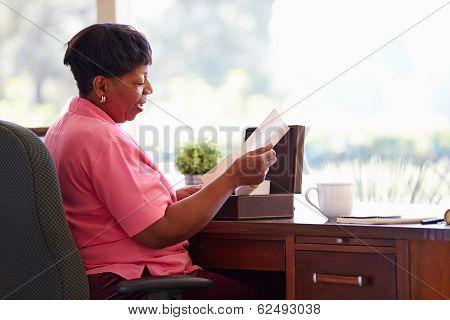 Mature Woman Putting Letter Into Keepsake Box