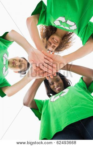 Environmental activists putting hands together smiling down at camera on white background