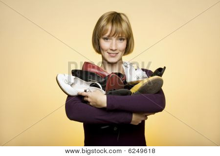 Young Woman Holding Many Shoes