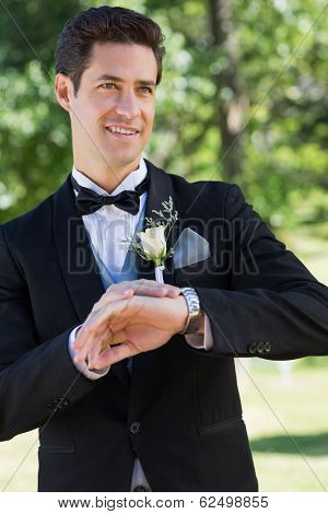 Smiling young bridegroom waiting in garden