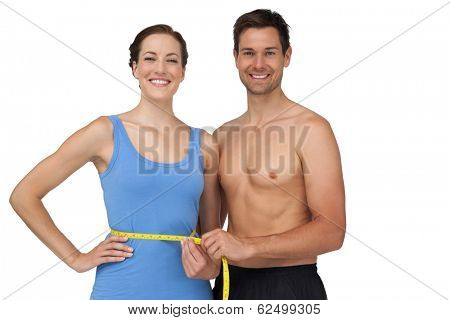 Portrait of a fit young man measuring womans waist over white background