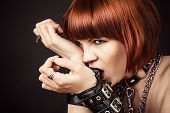 stock photo of sadomasochism  - beautiful sexy fashionable woman gnaws leather handcuffs - JPG