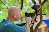 picture of paintball  - A man target practicing with a paintball gun / holding a paintball rifle