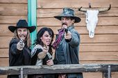 stock photo of threesome  - Old west trio screams and points guns - JPG