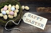 stock photo of bird egg  - Happy Easter candy easter eggs in birds nest on dark vintage recycled wood background with Happy Easter gift tag sign message greeting - JPG