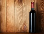 stock photo of liquor bottle  - Red wine bottle over wooden background with copy space - JPG