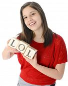 stock photo of lol  - A pretty young teen happily holding rustic alphabet blocks with her text - JPG